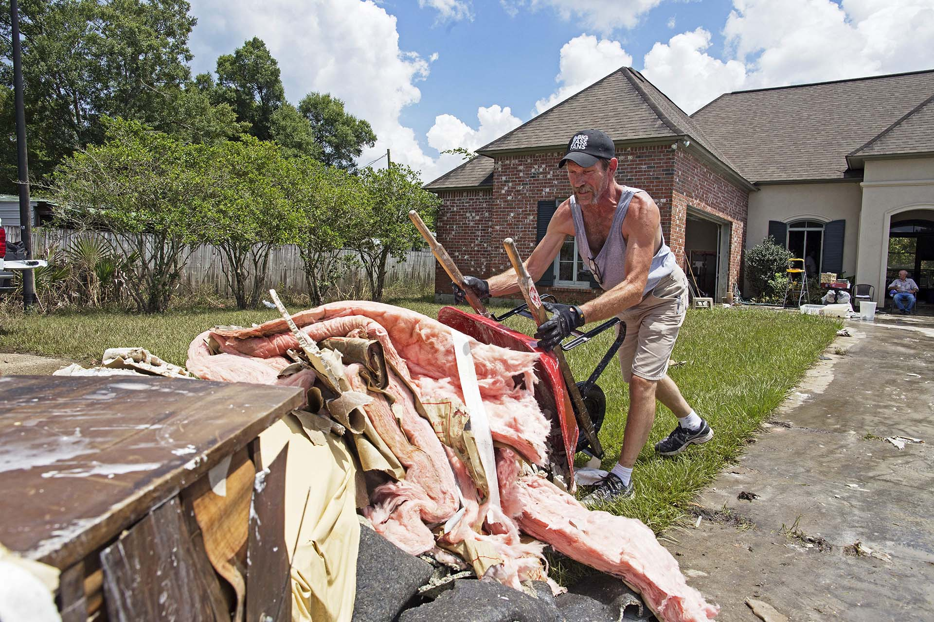 Jody Harelson, 52, dumps a wheel barrel of wet sheet rock an ever growing pile of rubbish as he helps clean out the flood damaged home of Sheila Siener, 58, in St. Amant, La., Saturday, Aug. 20, 2016.  Louisiana continues to dig itself out from devastating floods, with search parties going door to door looking for survivors.  (AP Photo/Max Becherer)